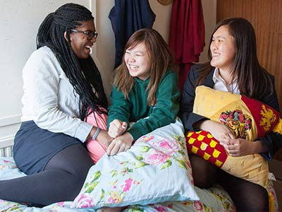 girls laughing in dormitory in boarding house