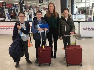 Sophie at airport with three students