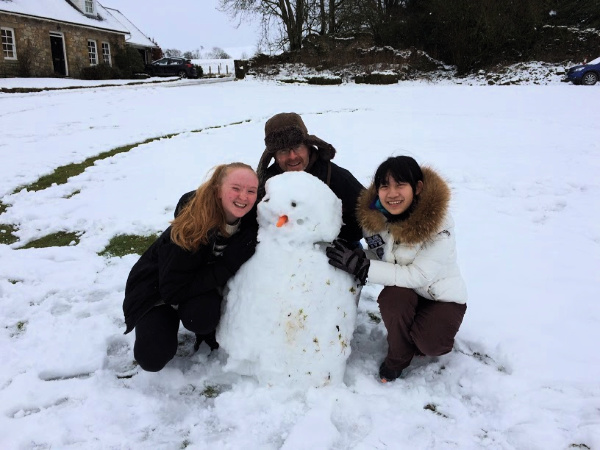 Host family building snowman with Chinese student
